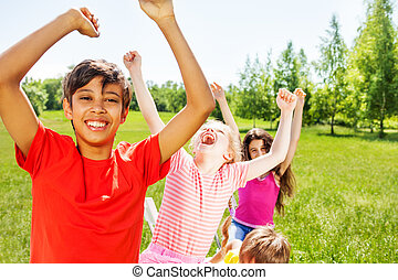 Happy kids with emotions and hands up in summer - Happy kids...