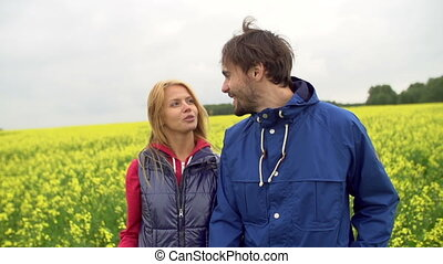Meadow Romance - Couple walking and talking leisurely in the...