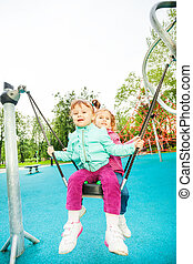 Two friends on swing set of playground in summer time