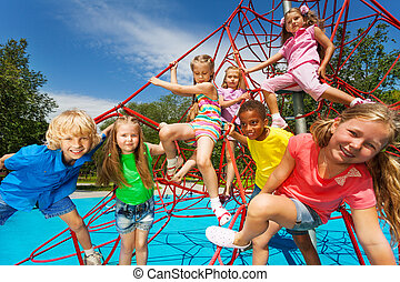 Happy group of kids on red ropes together in park - Happy...
