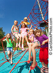 Many kids sit on red ropes of playground