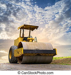 Road roller at road construction site with cloudy blue sky...