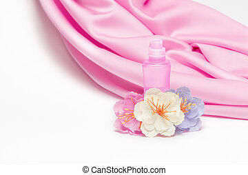 Perfume bottle with flowers on background of silk fabric