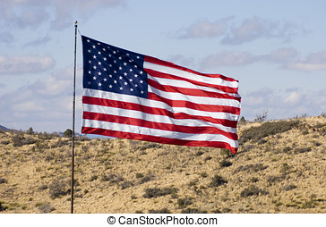 US Flag Flies Over High Desert Terrain - Close-up of a US...