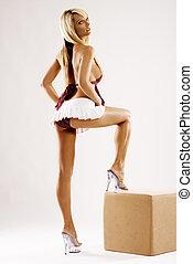 Slim tanned model in white skirt