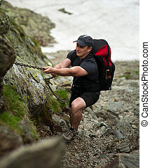 Climber with backpack - Man with heavy backpack climbing on...