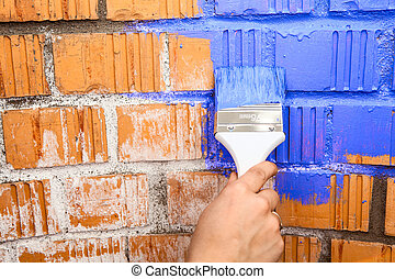 Human hand with blue colored brush painting brick wall -...