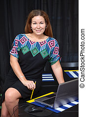 Pretty Caucasian business woman sitting on desk with opened laptop