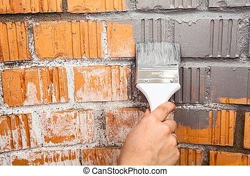 Human hand with grey colored brush painting brick wall -...