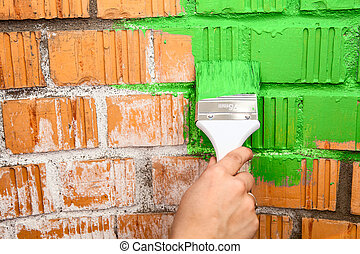 Human hand with green colored brush painting brick wall -...