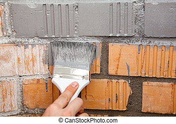 Paint brush with grey color on brick wall - Paint brush with...