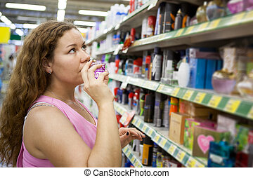 Woman purchaser smelling perfume in shop