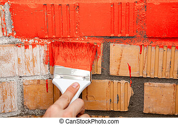 Paint brush with red color on brick wall - Paint brush with...