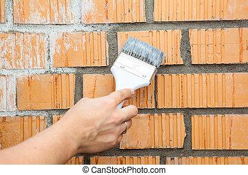 Caucasian hand starting to paint brick wall - Caucasian hand...