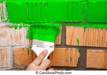 Paint brush with green color on brick wall - Paint brush...
