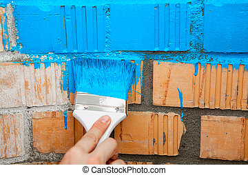 Paint brush with blue color on brick wall - Paint brush with...