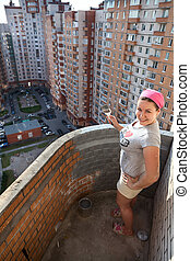 Woman painting balcony apartment on a high floor - Woman...
