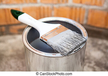 Paint brush in grey color laying on can - Paint brush in...