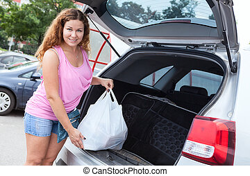 Pretty woman holding bag with food neaar trunk of pov