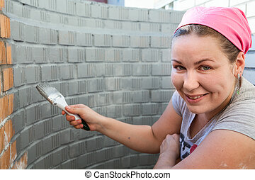 Woman with paint brush in hands painting a brick wall -...