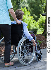 The nurse pushes the wheelchair of a disabled woman