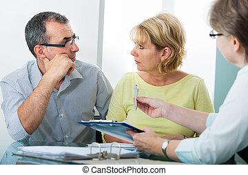 Credit counseling - Mature couple getting financial advice...