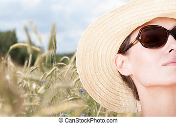 Beautiful woman on a meadow during sunny day