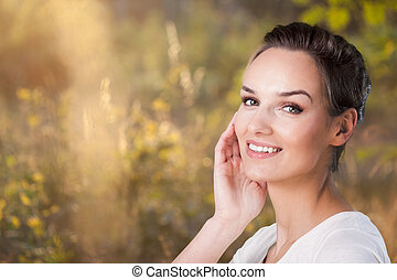 Smiling woman during sunny day on a meadow