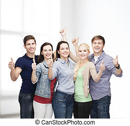 group of smiling students showing thumbs up - education and...