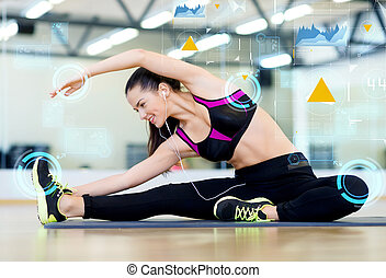 smiling young woman stretching on mat in gym - fitness,...