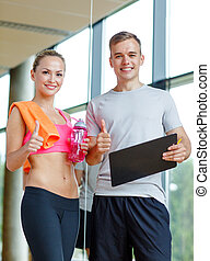 smiling young woman with personal trainer in gym - fitness,...