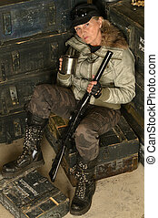 Armed combat female soldier in ammunition with a mug in his...