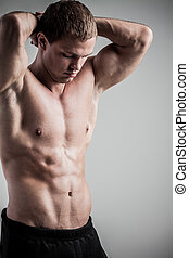 Fitness male model - Brutal athletic man posing on gray...