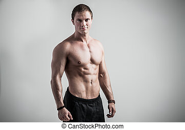 Fitness male model - Young athletic man posing on gray...