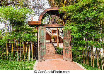 Wooden arched entrance with bamboo fence