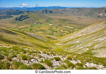 View plateau of Castelluccio with road on the mountain -...