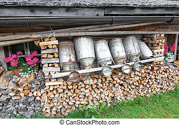 old milk cans in a alpine hut - old milk cans and firewood...