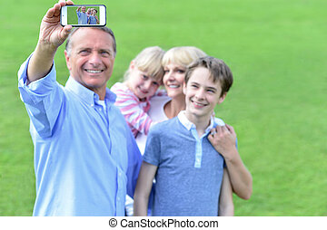Family capturing their enjoyment - Father taking a family...