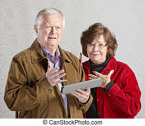 Perplexed Couple with Tablet - Perplexed man and woman...