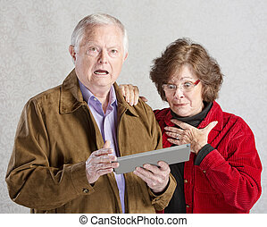 Startled Couple with Tablet - Startled man and woman looking...