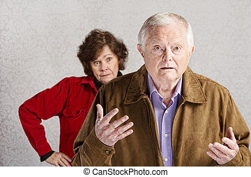 Bickering Couple - Frustrated older man with hands up and...