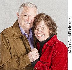 Embracing Senior Couple - Smiling Caucasian older couple...