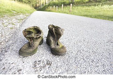 old hiking shoes - old worn hiking shoes on a street in the...