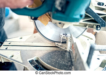 worker or handyman cutting PVC profile with circular...