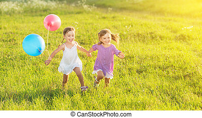 happy twin sisters running around laughing and playing with...