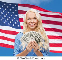 smiling young woman with us dollar money - finances and...