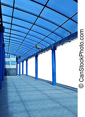 Exterior of a modern building with blue pillars and a...