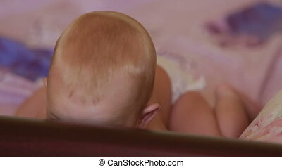 child blond lying on bed - lying on a bed of baby lifts his...