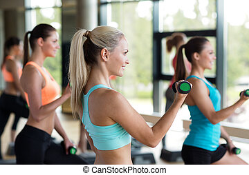 group of women with dumbbells and steppers - fitness, sport,...