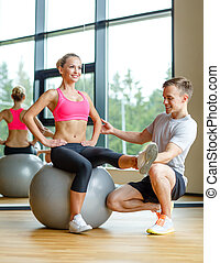 smiling man and woman with exercise ball in gym - sport,...